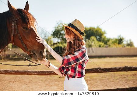 Smiling redhead young woman cowgirl taking care of her horse on farm