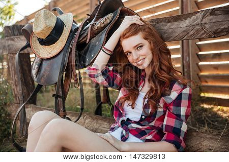 Happy attractive young woman cowgirl sitting on farm