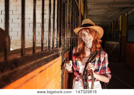Portrait of happy beautiful young woman cowgirl standing in stable