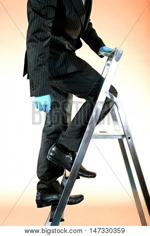 Side view low section of a businessman ascending corporate ladder against blue background