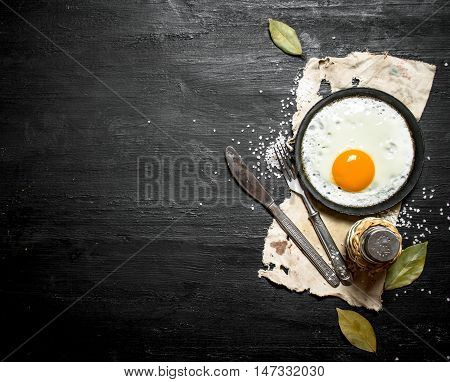 Fried egg with spices. On a black wooden background.