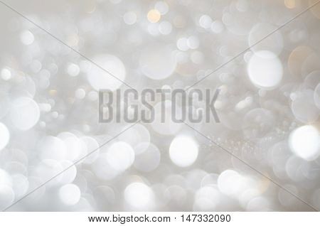A bokeh texture background of large and small circles in whites silver greys and soft copper gold.