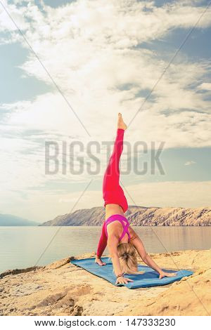 Girl meditating in yoga pose at the sea on rocks. Caucasian blonde woman exercising and training yoga peaceful stretching under cloudy morning sky. Fitness and exercising motivation and inspiration.
