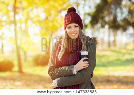 Closeup outdoor portrait of beautiful young blonde Caucasian woman wearing olive green parka jacket, knitted dark red scarf and beanie hat. Teenage girl in park in autumn holding takeaway coffee.