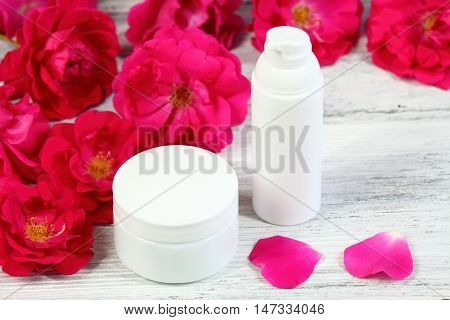 Cosmetic jars of face and body cream with red rose and rose petals provence style