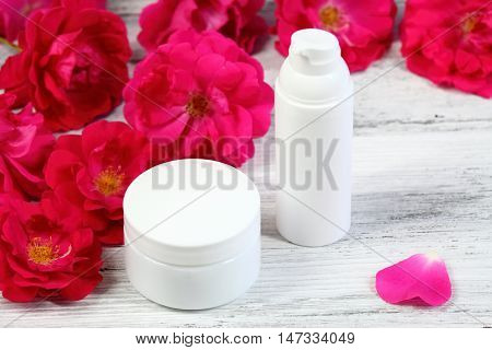 Cosmetic jars of face and body cream with red rose and a rose petal provence style