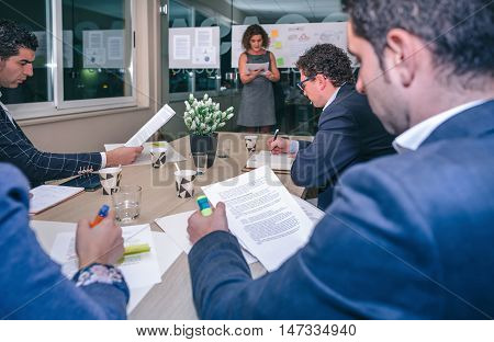Female coach talking while looking project management to business team sitting at table in headquarters