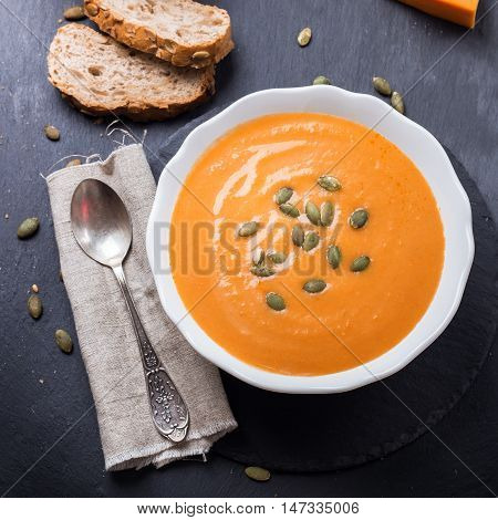 Still life, food and drink, seasonal concept. Autumn spicy pumpkin soup in a white bowl with grain cereal bread on a grunge black table. Selective focus, flat lay top view
