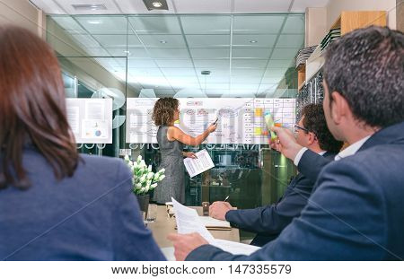 Female coach looking at business graph while businessman holding highlighter and having a question about diagrams