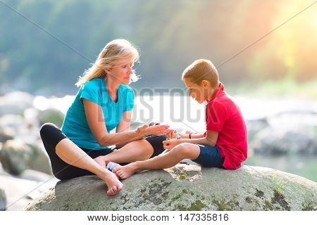 Alternative medicine. To a child with crystals therapy near a river in nature