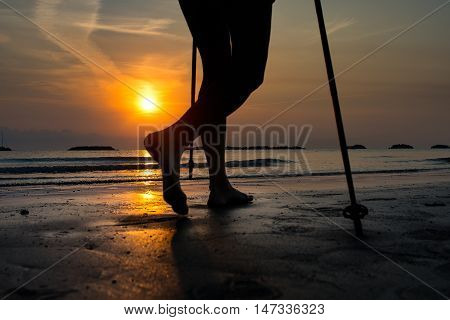 Particularly Of The Legs Of A Woman While Practicing Nordic Walking In The Beach At Sunrise