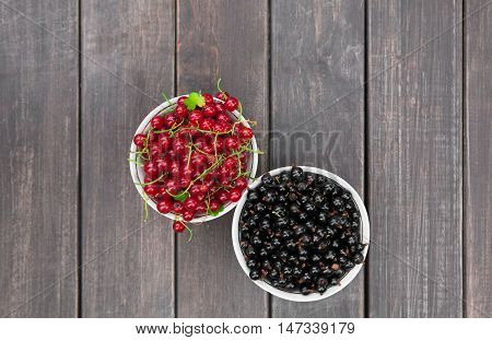 Fresh ripe black and red currants on rustic wood background. Bowl with natural organic berries with green peduncles on weathered grey wooden table, new berry harvest top view with copy space