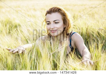 Sexy caucasian woman in the wheat cobs by sunset. Natural beauty. Backlight scene. Female portrait. Positive emotions.