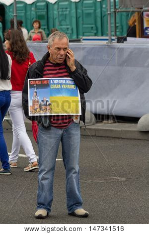 Kiev Ukraine - Auguct 24 2016: Man on Independence Square during the celebration of Independence Day holding a poster with an inscription Dogs bark and Ukraine is living! Glory to Ukraine