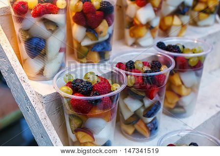 Plastic cups of sliced fruit. Strawberry, blackberry, kiwi, pineapple, raspberry, plum, grapes, melon for sale to go