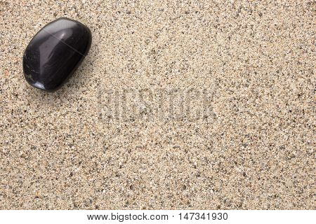 Black Basalt Stone On Sand Surface With Copy-space