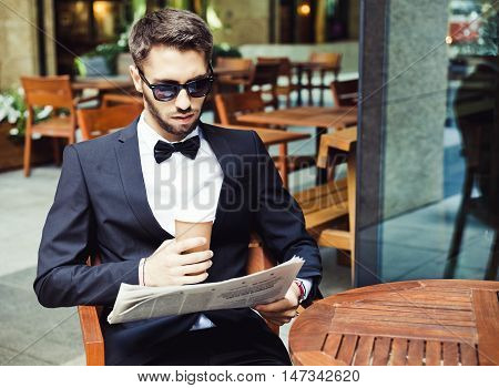 News and coffee. Young businessman reading the morning paper, drinking coffee in a cafe office building. Close up. Coffee break. Wall Street Exchange