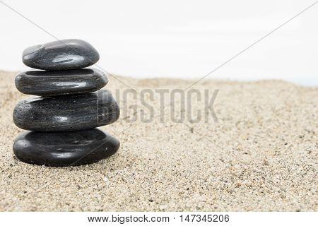Stack Of Black Basalt Balancing Stones On Sand, On White Background.