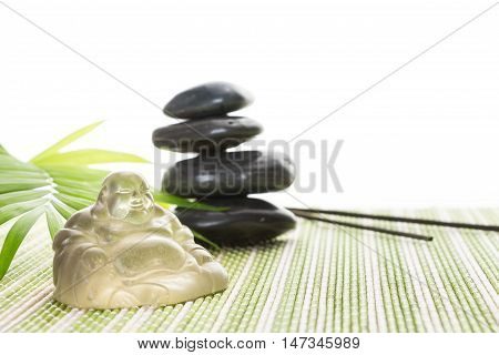 Glass Smiling Buddha With Stones And Leaves On Bamboo Mat, Isolated On White Background.