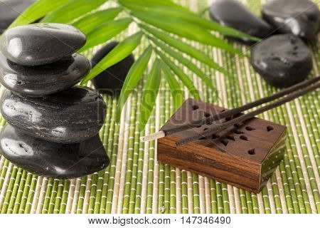 Stack Of Black Basalt Stones With  Incense Sticks And Green Leaf, On Bamboo Mat