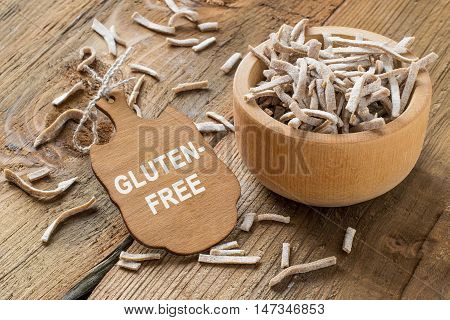 Homemade pasta from amaranth flour in a wooden bowl on the old wooden table. Gluten-free products. The source of vitamins and minerals. The concept of healthy and vegetarian food. Selective focus