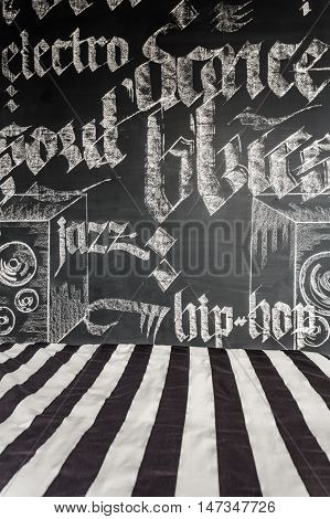 Shot of a black and white pattern bedding and chalkboard wall with hand-drawn music genres names