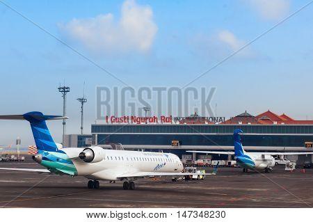 Denpasar International Airport Ngurah Rai Bali Island Indonesia - 31 August 2016: Aircrafts of national Indonesian air carrier Garuda in front of airport passenger terminal.