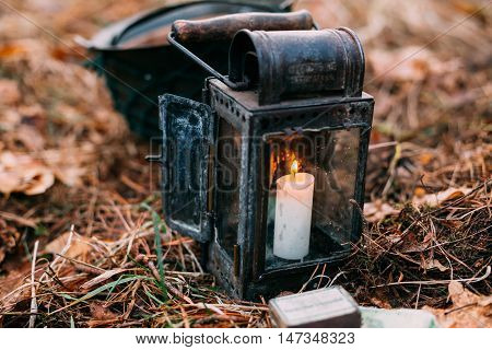 Old Vintage Lantern With Burning Candle On Forest Ground