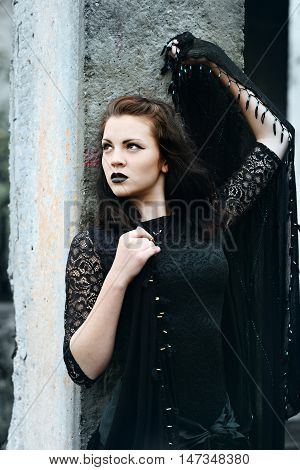 Young modern beautiful witch in the black shawl