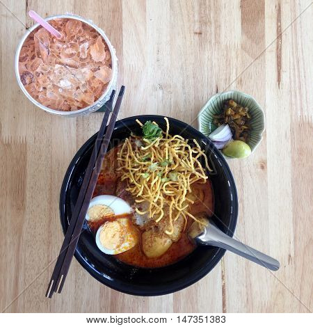 Chicken noodle with coconut milk and spicy soup Thai northern food ( khao soi ) with Thai Ice Milk Tea