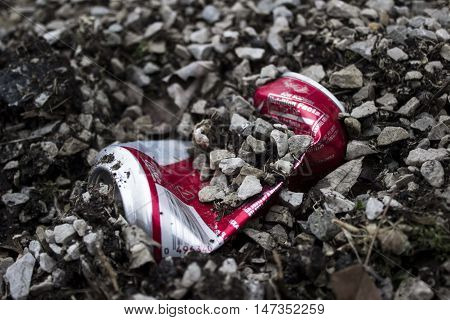 Aluminum can discarded in the gravel as trash