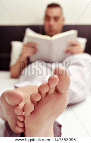 handsome young caucasian man wearing pajamas reading a book in bed