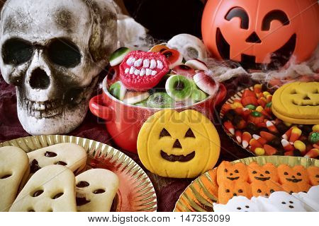 different Halloween candies and cookies on a table decorated with some scary ornaments, such as some skulls and cobwebs and a carved pumpkin