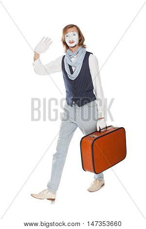 actor mime waves his hand walking with orange suitcase