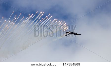 Fighter jet firing flares during a performance at the Dutch Air Force Open Day.