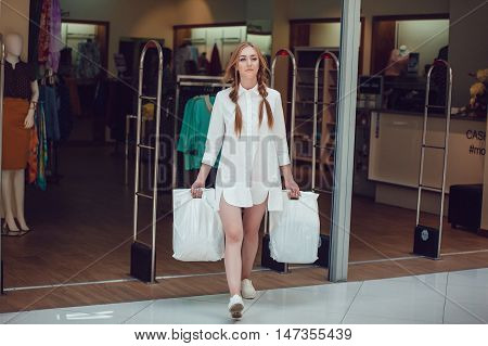 Girl coming out of the store after shopping with bags