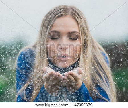 Teen girl poses for a high school senior portrait photo outdoors blowing glitter