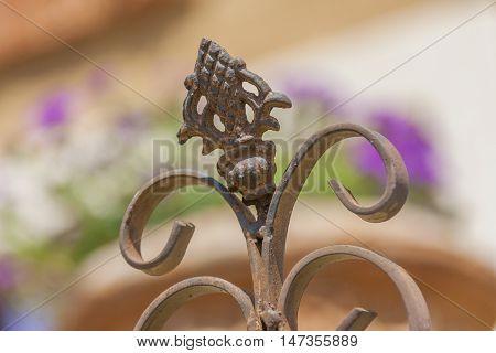 Metal rusty curls in garden detail patina purple in background