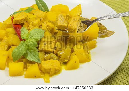 stew meat with potatoes  and vegetables,  beef stew yellow, garnished with mint leaves, meat pricked on a fork