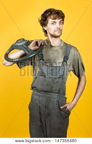 Handsome smiling mechanic in work clothes keeps the wheel on his shoulder and posing on the background of yellow bright wall