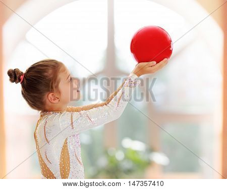 On the background of the hall with large semi-circular window.Cute little girl gymnast turned sideways to the camera , holding in his outstretched hands a red ball.