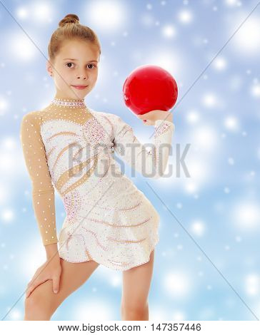 Beautiful little girl gymnast in elegant dress, posing with a red ball.On a blue background with large, white, Christmas or new year's snowflakes.