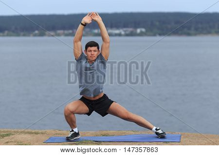 Man doing yoga outdoor. Young man practicing yoga fitness exercise outdoor at beautiful sea. Meditation and relaxation