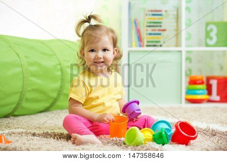 Cheerful kid toddler playing in nursery room