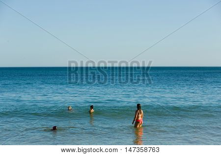 ALBUFEIRA, PORTUGAL - AUGUST 20, 2016: People at the famous beach of Olhos de Agua in Albufeira. This beach is a part of famous tourist region of Algarve.