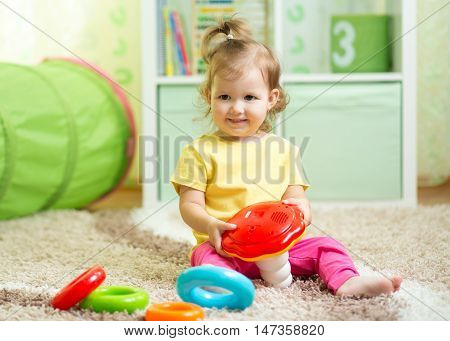 Cute child toddler sitting on floor with toys in playroom