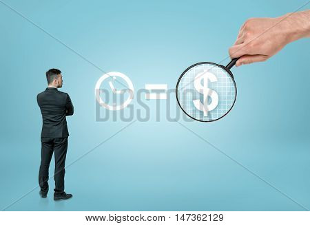 Back view of a businessman looking at sigh 'time is money' with big man's hand enlarging dollar sign with a magnifier. Benefit and success. Wealth and prosperity.