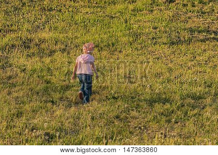 child goes across the meadow with cut grass