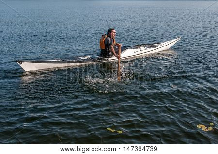 man sculling back with a kayak on a lake - serial pictures