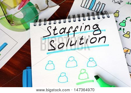 Notepad with staffing solutions on a wooden surface.